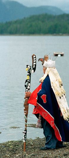 Man dressed in ethnic clothing overlooking lake