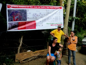 A family stands under a banner showing the proposed mining licenses in their communities. La Puya, Guatemala